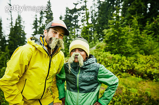Portrait of father and son with mustaches made of moss during camping trip - gettyimageskorea