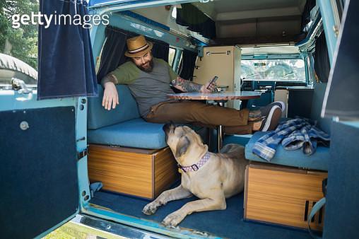 Man relaxing with dog in camper van - gettyimageskorea