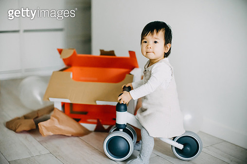 Joyful baby girl unwrapped her Christmas present and can't wait to ride on her bicycle - gettyimageskorea