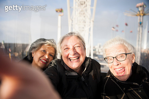 Three senior girlfriends laughing and taking a selfie in the ferris wheel at the fair in Amsterdam. City in the background. Mixed group of girlfriends, varying both in age and ethnicity. - gettyimageskorea