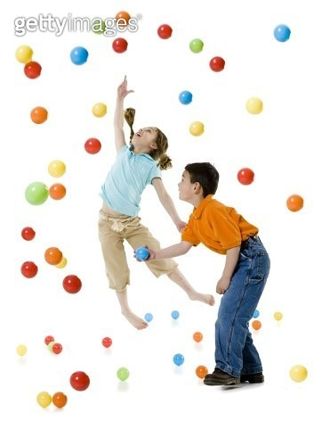A boy and a girl playing with colorful balls - gettyimageskorea