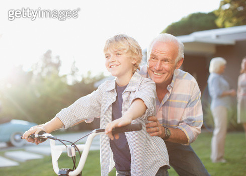 Older man helping grandson ride bicycle - gettyimageskorea