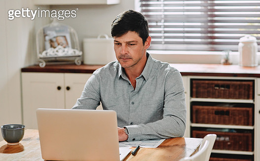 Cropped shot of a man using his laptop while sitting at home - gettyimageskorea