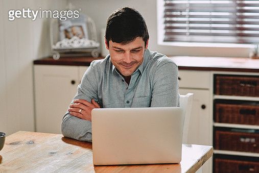 Cropped shot of a man smiling while using his laptop - gettyimageskorea