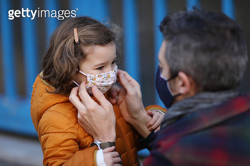 A father putting a protective face mask on his little daughter in front of school - gettyimageskorea