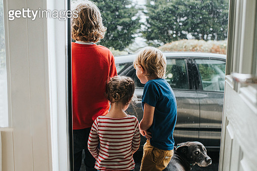 Three Kids and a Dog standing outside Front Door looking at Heavy Rain - gettyimageskorea