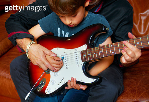 Father teaching son to play the guitar - gettyimageskorea