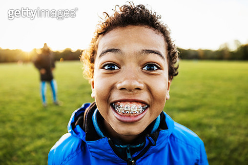 A close up of a young boy smiling while spending the day with his dad at the park. - gettyimageskorea