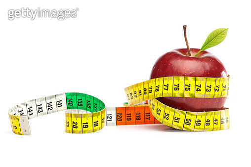 Close-Up Of Tape Measure Rolled On Apple Over White Background - gettyimageskorea