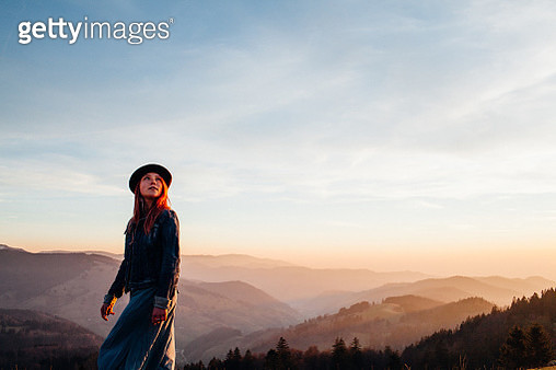 Young woman with hat on mountain at sunset - gettyimageskorea