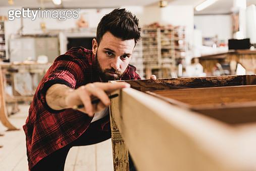 Man examining wood in workshop - gettyimageskorea
