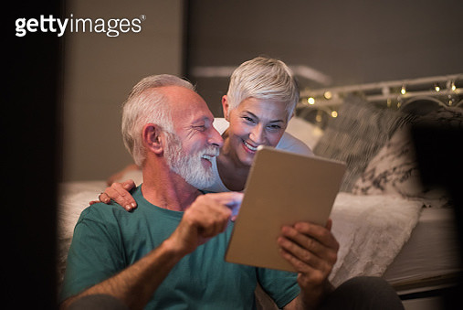 Couple using digital tablet and smiling - gettyimageskorea