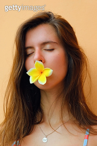 Young woman with a flower in her mouth on a colored background - gettyimageskorea