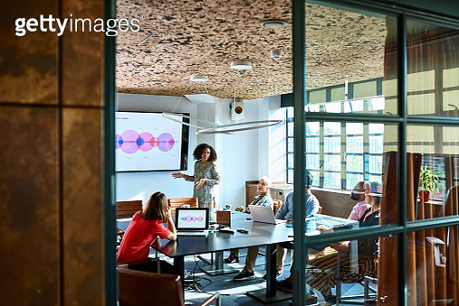Female team leader standing in board room, providing feedback on business strategy to multi racial colleagues, forecasting and projecting - gettyimageskorea