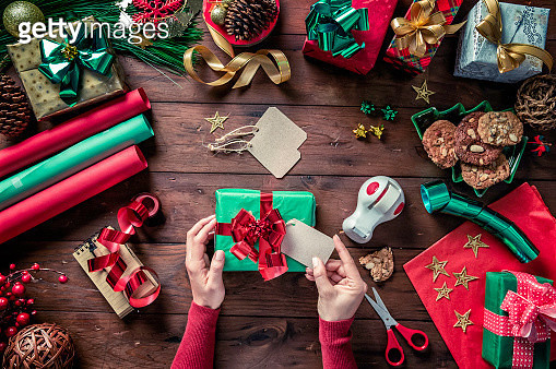 Top view of woman hands placing label on gift box. Christmas themes. - gettyimageskorea