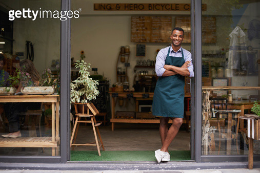 A handsome young man standing in the entrance to his store - gettyimageskorea
