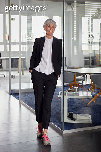 Portrait of fashionable senior businesswoman wearing pantsuit and sneakers in office - gettyimageskorea