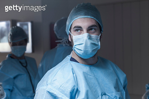 Portrait of surgeon wearing mask with team in background - gettyimageskorea
