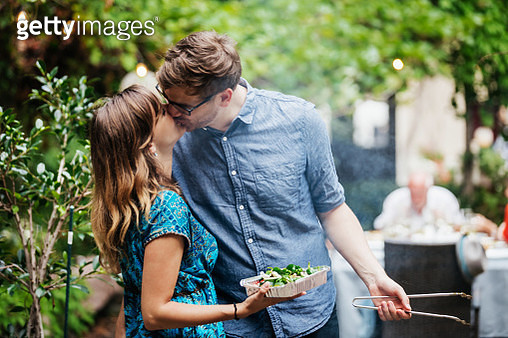 A couple tenderly kissing while cooking togehter at a family barbecue. - gettyimageskorea