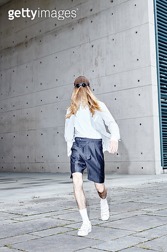Portrait of handsome man with long blond hair wearing white shirt and grey shorts walking on concrete surface. - gettyimageskorea