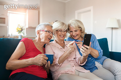 Three Female Senior Friends Having Fun With Mobile Phone in the Living Room. Ageing Women Using Smartphone or Mobile Phone Share Social Media Together in Wellbeing. Group of Happy Elderly Female Senior Society Lifestyle Technology Concept - gettyimageskorea