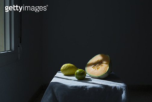 Still life of cantaloup, lime and lemon in shady light coming from a window - gettyimageskorea
