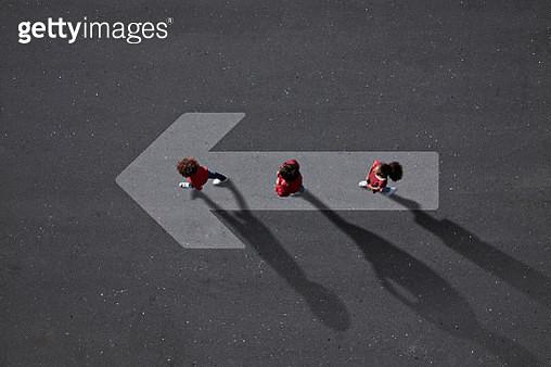 School children dressed in red, walking across big painted arrow - gettyimageskorea