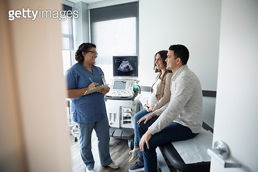 Female nurse talking with pregnant couple in clinic examination room - gettyimageskorea
