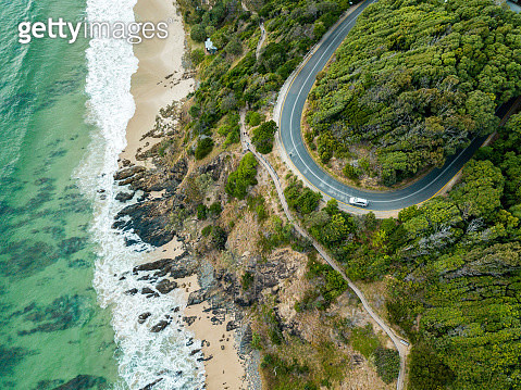 rocky outcrop into ocean with road - gettyimageskorea