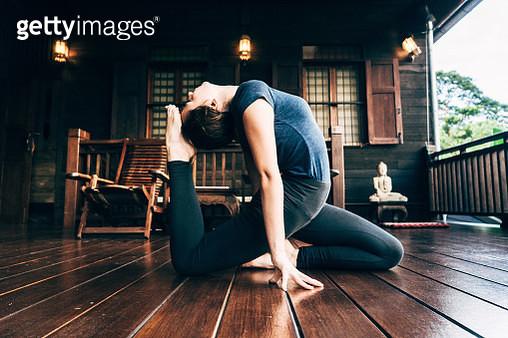 Woman doing yoga on balcony - gettyimageskorea