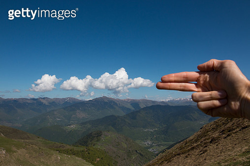 Man's fingers pointing like a gun simulating a gunshot with the clouds in a mountain landscape - gettyimageskorea