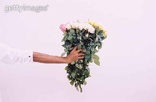 Extended arm holding assortment of flowers - gettyimageskorea