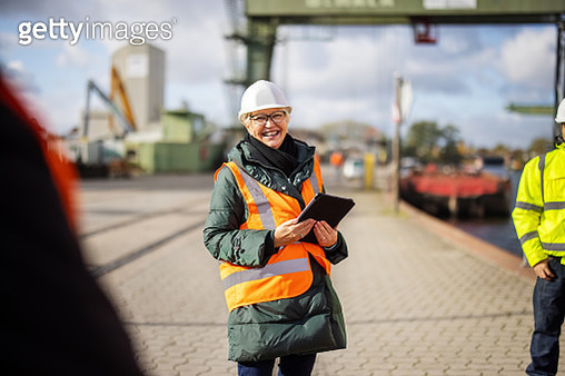 Smiling manager having a meeting with dock workers - gettyimageskorea