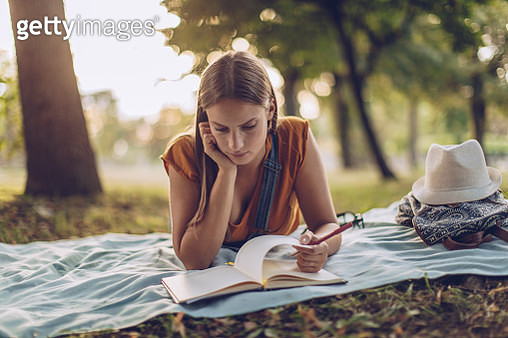 Cute woman reading in park - gettyimageskorea