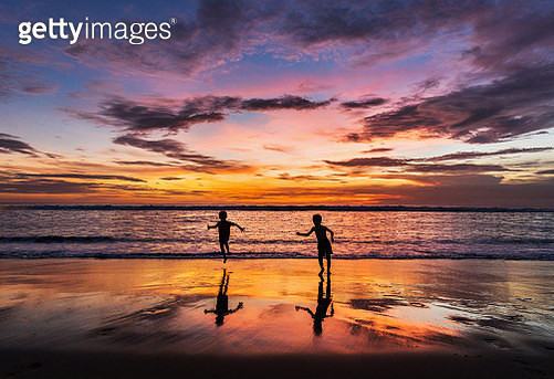 Silhouettes of small kids having fun while running on the beach at sunset. Copy space. - gettyimageskorea