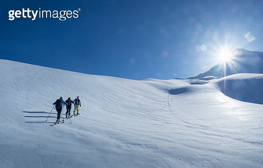 Climbers with ski ascending a snowy slope under sunshine in a bright winter sunny day. - gettyimageskorea