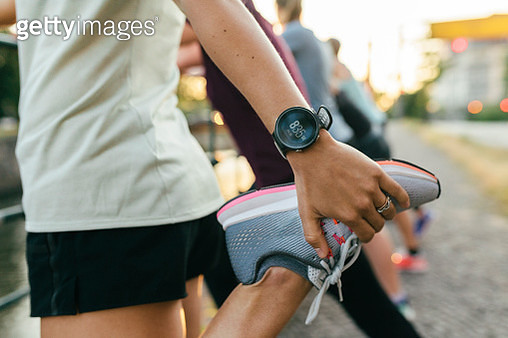 A close up of a woman stretching her legs before going on a run through the city. - gettyimageskorea