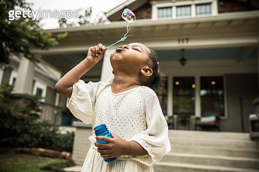 Young girl (3 yrs) blowing bubbles outside of home - gettyimageskorea