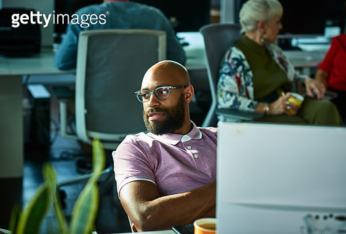 Candid portrait of African businessman wearing glasses looking away in office - gettyimageskorea