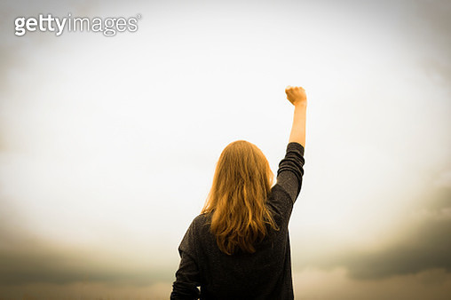 Rear view of woman with fist in the air. - gettyimageskorea