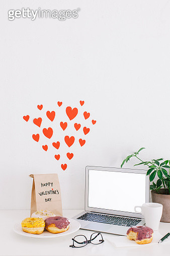Still life with laptop, donuts, Valentines day present and hearts on wall - gettyimageskorea