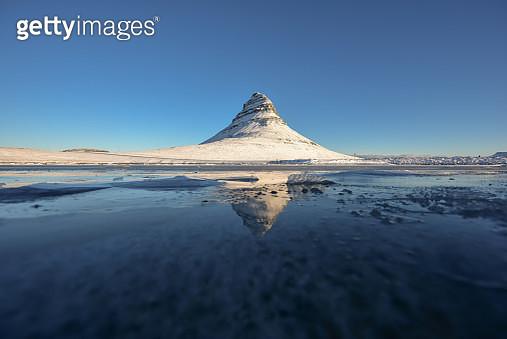 The Kirkjufell Mountain reflected in a lake in Iceland. - gettyimageskorea