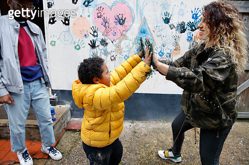 Mother and son touching hands covered in wet paint - gettyimageskorea