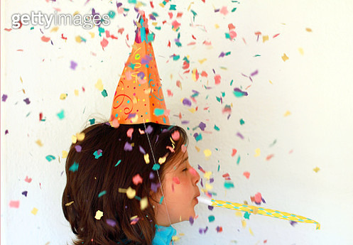 Girl blowing party blower with colorful confetti. Celebration concept - gettyimageskorea