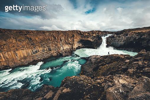Man exploring Aldeyjarfoss waterfall surroundings in Iceland. - gettyimageskorea
