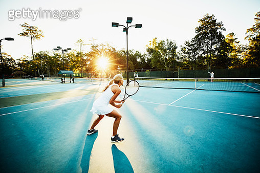 Mature female tennis player preparing to return ball during early morning tennis match - gettyimageskorea