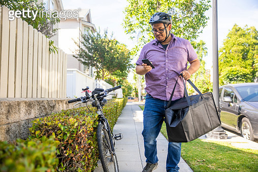 A young Hispanic man delivers food with his bicycle. - gettyimageskorea