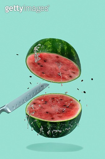 Watermelon sliced with knife are flying with splash on pastel green background. Minimal fruit and summer concept. - gettyimageskorea