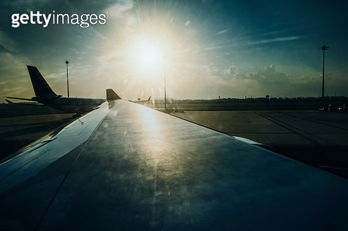 View looking from the airplane window in the airport. Wing of an airplane against shining sun during sunrise - gettyimageskorea