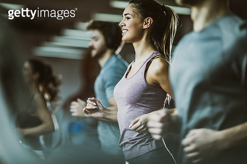 Happy female athlete jogging on treadmill in a gym full of people. - gettyimageskorea